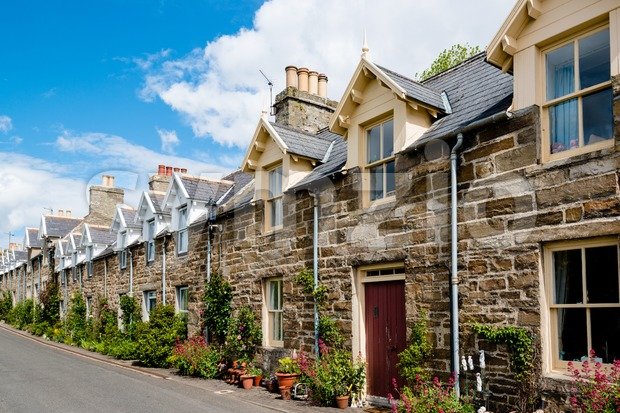 Row of traditional stone houses in a scottish village in front of great cloudy sky