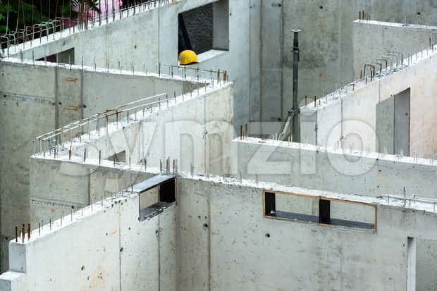 New walls being erected on a construction site with steel enforcements, scaffolding and a yellow builder helmet