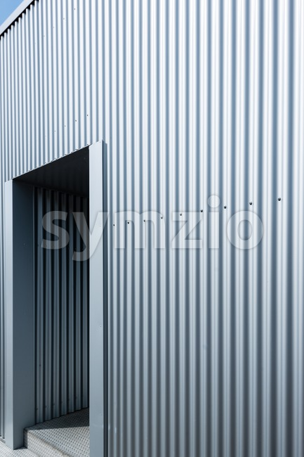 Exterior of a modern metal commercial warehouse with entrance