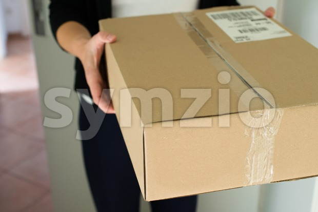 Woman picking up a parcel at her flat
