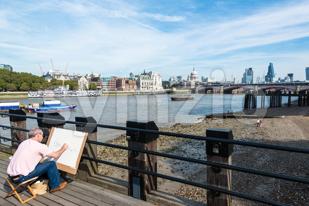 LONDON, UK - SEPTEMBER 28, 2014: An artist on the South Bank of river Thames is painting the skyline from ...