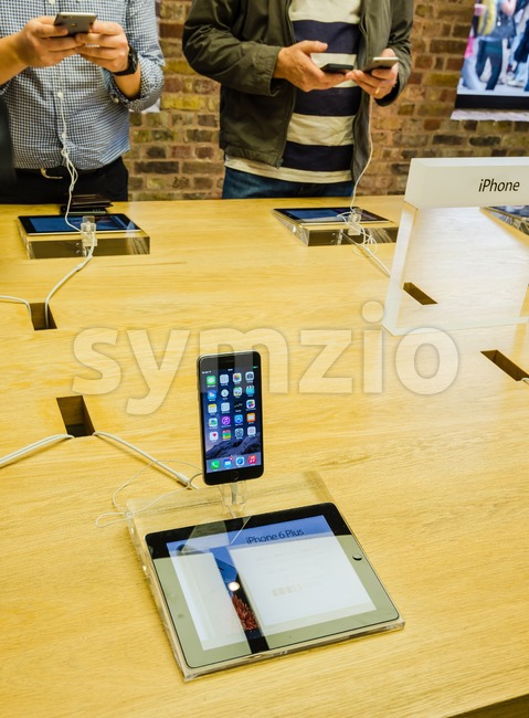 LONDON, UK - SEPTEMBER 26, 2014: Customers admiring the new Apple iPhone 6 and iPhone 6 Plus at the Apple ...