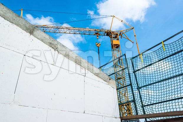 A yellow tower crane at construction site with great blue sky