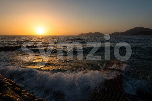 Red sky over a rocky seashore. Sunset landscape with high waves