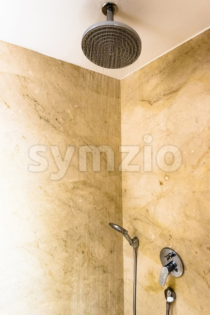 Contemporary bathroom with marble and head shower while running water
