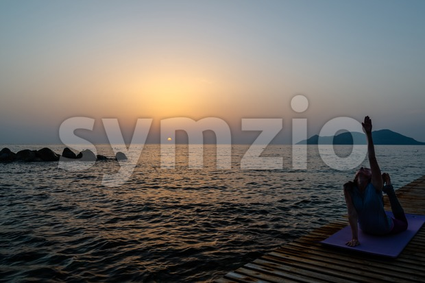 Woman practicing yoga on the beach at sunset Stock Photo
