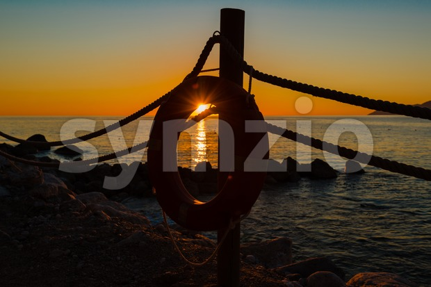 Lifebuoy and sundown Stock Photo