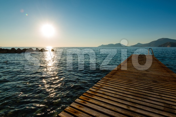 Jetty and island in sunset Stock Photo