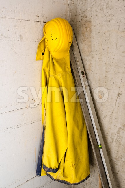 Work wear on construction site: yellow hard hat and raincoat hanging on a freshly errected wall