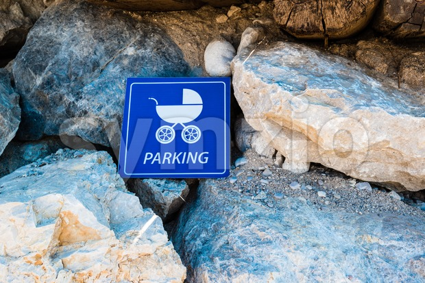 Baby carriage parking sign mounted on rocks at the beach