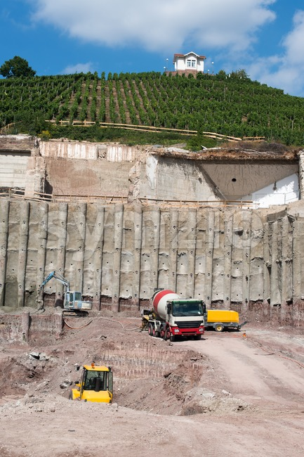 Construction site with various machinery and concrete construction into the hill and beautiful villa above vineyards with great blue sky