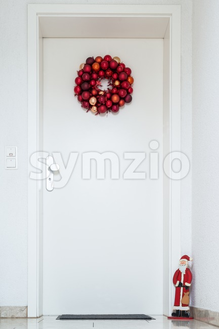 Christmas wreath decorated with red balls and Santa Claus on white entrance door to a flat