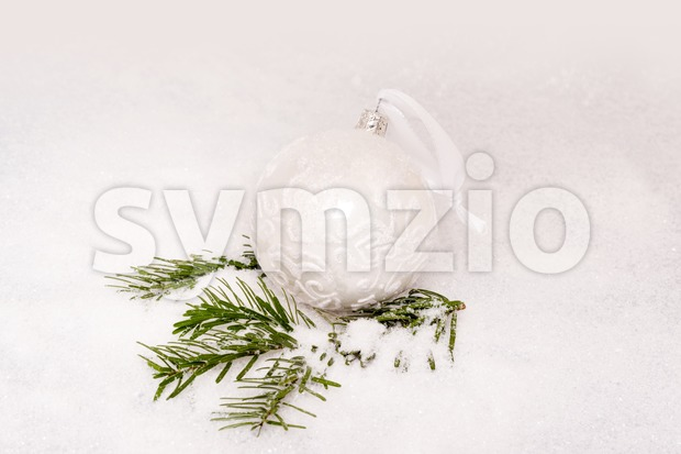 Closeup of  Christmas ball and fir branch with artificial snow and space for your text