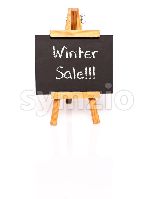 Winter Sale. Blackboard with text and easel. Photo on white background with shadow and reflection.