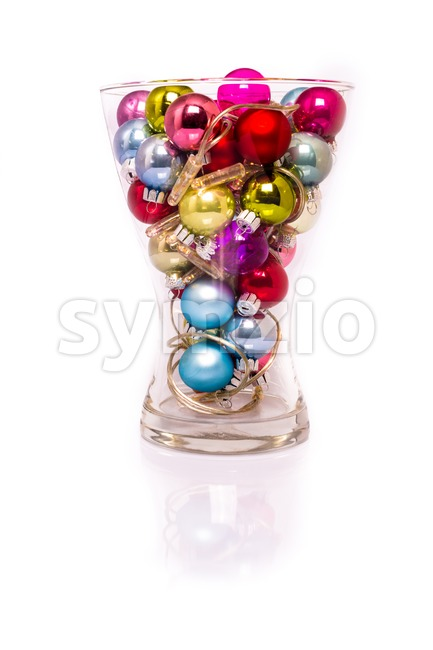 A collection of Christmas fairy baubles with lights in a vase with reflection and shadow in white background