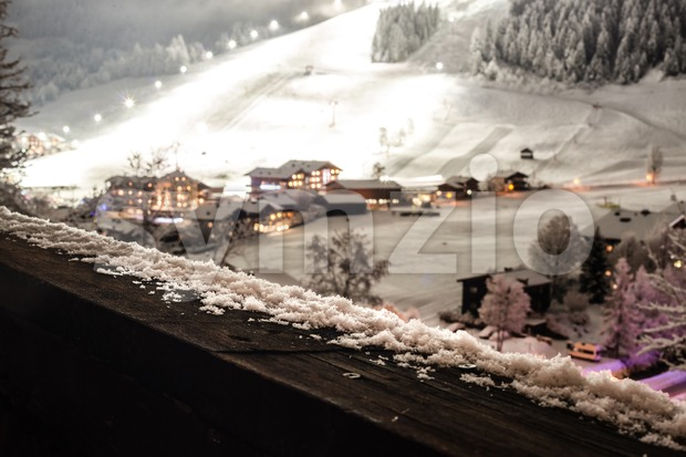 Picturesque winter scene of snow on wooden balcony railing with view on a ski village at night