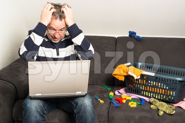 Reconciliation of work and family life: Portrait of a frustrated middle aged man sitting in front of computer with toys ...