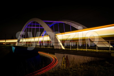 Railway bridge with train and car lights  at night Stock Photo