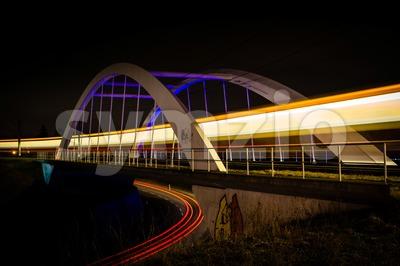 Railway bridge with train and car lights  at night Stock Photo