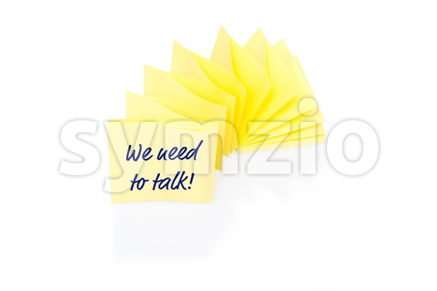 Yellow sticky note on block with message We Need To Talk Stock Photo