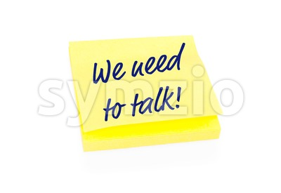 Yellow sticky note on block with text We Need To Talk Stock Photo