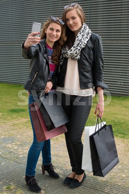 Two attractive young women making a selfie outside of the shopping mall carrying their bags