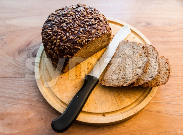 Fresh baked bread with knife and cut slices on cutting board, on wooden background