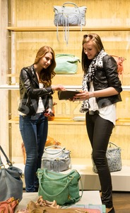 Two young girls shopping for handbags Stock Photo