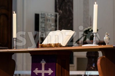 Open Bible and candles on the altar of a church Stock Photo