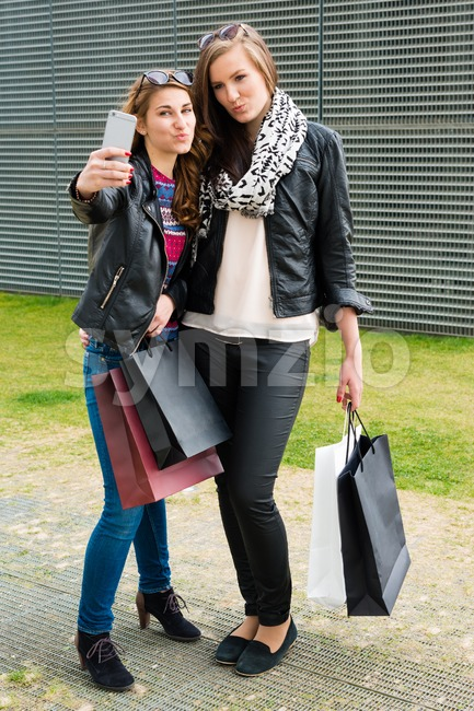 Two attractive girls making a selfie after shopping Stock Photo