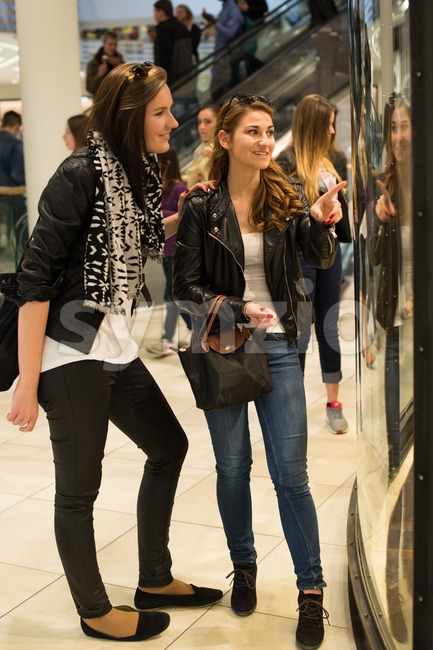 STUTTGART, GERMANY - MARCH 21, 2015: Two attractive young women are looking through a shop window in a mall while ...