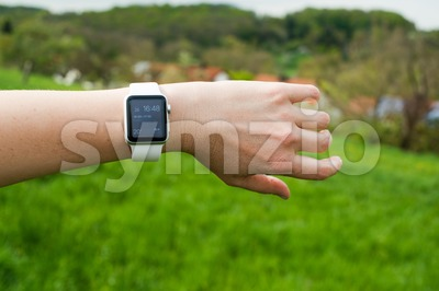 Woman checking her Apple Watch in the green Stock Photo