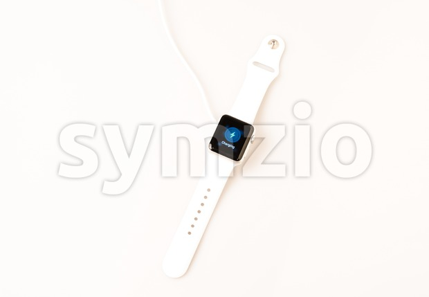 OSTFILDERN, GERMANY - APRIL 26, 2015: Charging the new Apple Watch: A white 38mm Apple Watch Sport is being charged ...