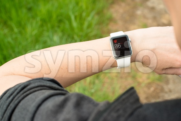 Woman checking her pulse using the Apple Watch Stock Photo
