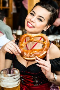 Woman in Dirndl eating Oktoberfest Pretzel Stock Photo