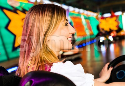 Beautiful girl in an electric bumper car in amusement park Stock Photo