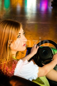 Beautiful girl in an electric bumper car in amusement park Stock Photo