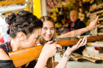 Two attractive girls playing shooting games at German funfair Stock Photo