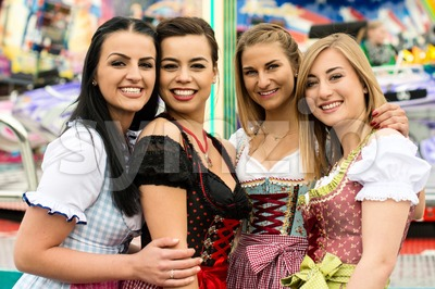 4 gorgeous young women at German funfair Stock Photo