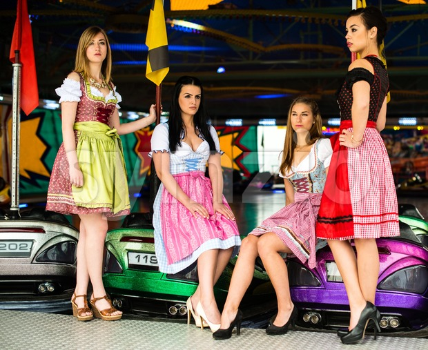 Joyful young and attractive women at German funfair Oktoberfest with traditional dirndl dresses and bumper car in the background. Mixed ...