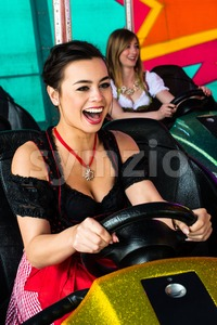 Beautiful girls in an electric bumper car in amusement park Stock Photo