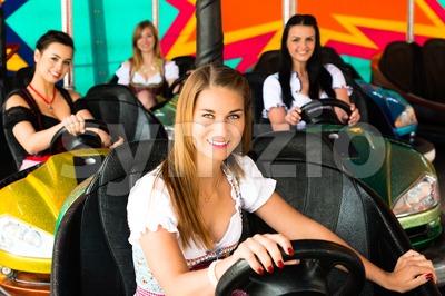 Beautiful girls in an electric bumper car in amusement park Stock Photo