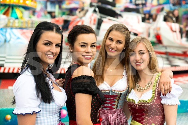 Joyful young and attractive women at German funfair Oktoberfest with traditional dirndl dresses and joyride in the background. Mixed nationalities, ...