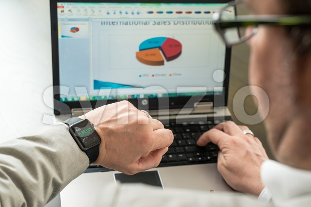 Businessman checking stock market prices on his Apple Watch Stock Photo