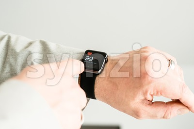 Businessman checking his pulse using the Apple Watch Stock Photo