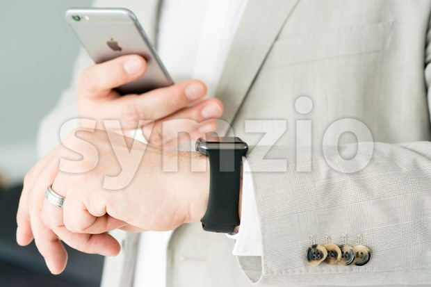 Businessman using the Apple Watch and an Apple iPhone 6 Stock Photo