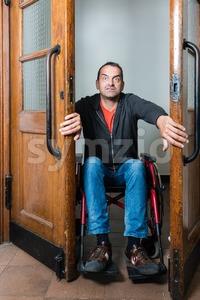 Man in wheelchair stuck between swing doors Stock Photo