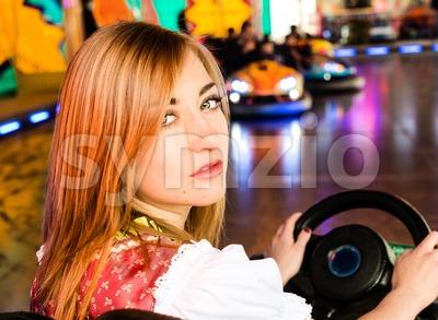 Beautiful girl in an electric bumper car at amusement park Stock Photo