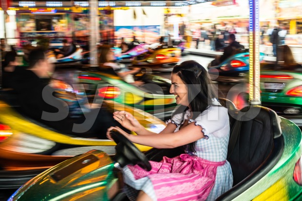 Beautiful girl in an electric bumper car at amusement park Stock Photo