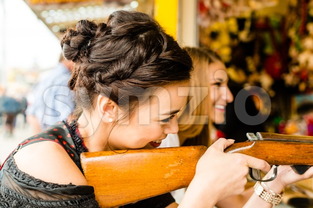 Two attractive girls playing shooting games at German funfair Oktoberfest. Both wearing traditional Dirndl dresses, the one in front having ...